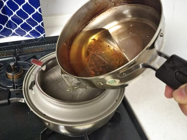 天ぷら鍋の油をこしている画像